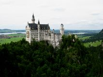 Fairy tales castle. A white castle on top of a hill with the forest all around as the typical castle that people think of in fairy tales Royalty Free Stock Image