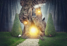 Fairy tree house in dark fantasy forest Stock Photos