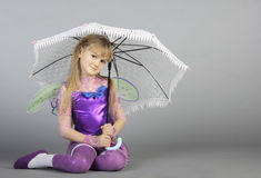 The fairy with an umbrella. The girl in a suit of the fairy under a summer umbrella Royalty Free Stock Photos
