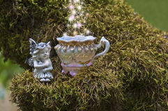 Fairy watching sparkles of light flow into fairy wish cup. Fairy sitting on mossy branch next to a magical fairy teacup. There are whimsical sparkles of light Royalty Free Stock Photography