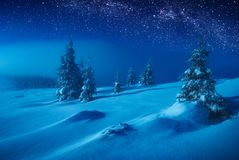 Fairy winter valley covered with snow in a moon light. Milky way in a night starry sky. Christmas and New Years mood Royalty Free Stock Photography