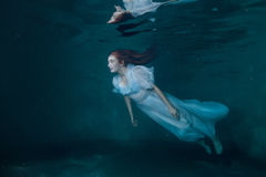 Fairy woman in white dress underwater. Royalty Free Stock Images