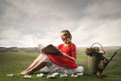 Fairytale atmosphere. Pretty girl reading a huge book, sitting in a field in a fairytale atmosphere Royalty Free Stock Photography