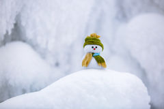 Fairytale character the snowman in hat and scarf. Fairytale character the snowman in hat and scarf is standing on fascinating fluffy snow near the hill and Royalty Free Stock Image