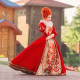 Fairytale countess in castle. Young baroque redhead queen with historical hairsdo. Renaissance princess with red hair. Fairytale queen in red gown with collar royalty free stock photos