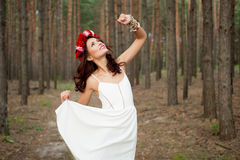 Fairytale in forest. Fairytale in the forest. Beautiful woman wearing white dress and with red roses hairband in pine forest royalty free stock photography