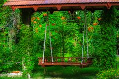 Fairytale garden with flowers and a couple swing. This unique picture shows a fairytale garden with an old park bench. This picture was taken in the Maldives royalty free stock images