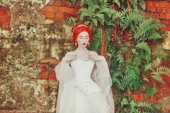 Fairytale hero. Renaissance redhead princess with hairstyle in castle. Fabulous rococo duchess in white dress against the backdrop. Of old fern wall. Duchess in stock photo