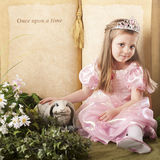 Fairytale Princess. A beautiful preschool princess petting a bunny before a Once upon a time storybook stock photos