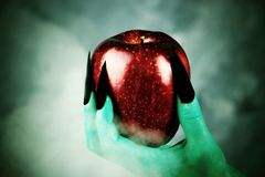 Beautiful red apple in green hands of old witch with black nails. Fairytale scary. mystical and fantasy scene with green hands and red apple stock photos