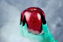 Beautiful red apple in green hands of old witch with black nails. Fairytale scary. mystical and fantasy scene with green hands and red apple stock image