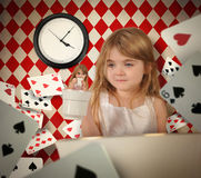 Fairytale Teacup Girl with Floating Playing Cards. A little child is holding up a tea cup with herself inside with playing cards floating around her for a stock image
