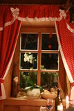 Fairytale window with red curtains. Decorated with stars and christmas decorations Royalty Free Stock Photos