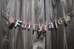 Fairytale. The word 'Fairytale' hanging on a string against a fence Royalty Free Stock Photo
