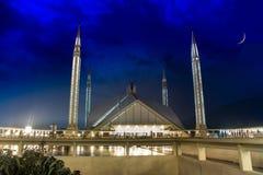 Faisal Mosque in de Duisternis van de nacht met een perfecte halve maan in de hemel royalty-vrije stock afbeelding