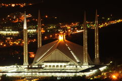 Faisal Mosque at night. A night view of Faisal mosque, islamabad pakistan, and view of city lights in background royalty free stock images