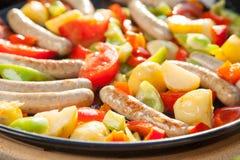 Faisant cuire de petites saucisses, pommes de terre et tomates dans une casserole chaude coooking dehors au soleil Photographie stock