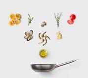 Faisant cuire des ingrédients pour la nourriture italienne, pâtes de fruits de mer, sur le blanc Images stock