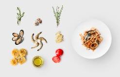 Faisant cuire des ingrédients pour la nourriture italienne, pâtes de fruits de mer, sur le blanc Photographie stock libre de droits