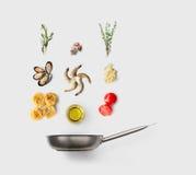 Faisant cuire des ingrédients pour la nourriture italienne, pâtes de fruits de mer, sur le blanc Image stock