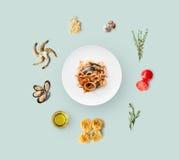 Faisant cuire des ingrédients pour la nourriture italienne, pâtes de fruits de mer, sur le bleu Photo libre de droits