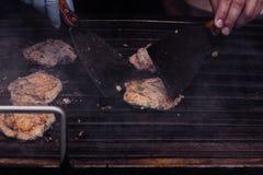 Faisant cuire les hamburgers délicieux de poissons sur le gril extérieur Photographie stock