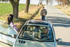 Faisant de l'auto-stop l'amie stationnée de véhicule offrent le levage Photos stock