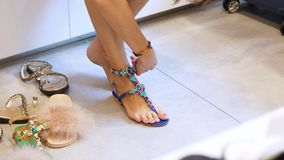 Faisant des emplettes dans le magasin, faisant des emplettes plan rapproché, pied femelle en sandales dans un magasin de chaussur clips vidéos