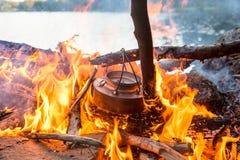 Faisant le café sur le camp mettre le feu près de l'eau Image stock