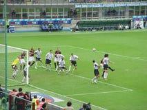 Faisant le coin donnez un coup de pied dedans un football de Milan   Photographie stock