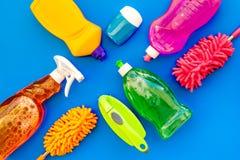 Faisant le ménage avec les détergents, le savon, les décapants et la brosse dans des bouteilles en plastique sur la maquette bleu photos stock