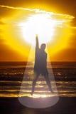 Faisceau faisant de la lévitation de Sun d'énergie de silhouette d'homme de mer Images stock