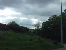 Faisceaux de lumière du soleil par des nuages Image stock