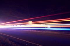 Faisceaux lumineux colorés des véhicules mobiles sur la route occupée au crépuscule image stock