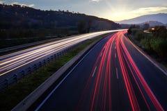 Faisceaux lumineux des véhicules sur la route Images stock