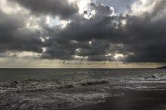 Faisceaux par des nuages à la mer Photo libre de droits