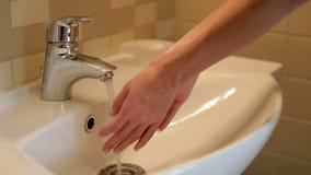 Fait couler l'eau et commence à se laver les mains sous l'eau clips vidéos