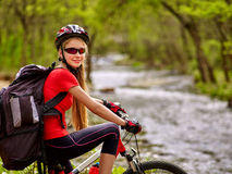 Fait du vélo la fille de recyclage avec le passage de gué de recyclage de grand sac à dos dans toute l'eau Photographie stock