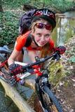 Fait du vélo le passage de gué de recyclage de recyclage de fille dans toute l'eau sur le rondin Image stock