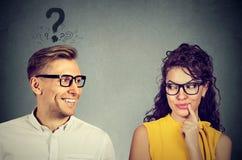 Fait elle m'aiment ? Homme avec le point d'interrogation regardant une fille attirante flirtant avec lui Photos libres de droits