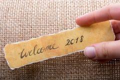 Faites bon accueil à 2018 libellés écrits sur un papier déchiré jaune Photo stock