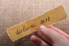 Faites bon accueil à 2018 libellés écrits sur un papier déchiré jaune Photographie stock