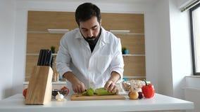 Faites cuire dans la cuisine moderne coupant une courge sur la table en bois banque de vidéos
