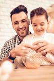 Faites cuire Food à la maison Famille heureux Jour du `s de père Cuisinière Food de fille et d'homme Homme et enfant de sourire a photo libre de droits