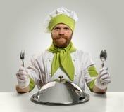 Faites cuire le chef avec le plateau de fourchette, de cuillère et de nourriture sur le fond d'isolement Image stock