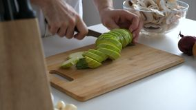 Faites cuire les mains coupant une courge sur la table en bois clips vidéos