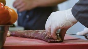 Faites cuire les mains du ` s coupant en grand morceau de viande crue utilisant un couteau du ` s de boucher banque de vidéos