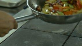 Faites cuire mélanger les légumes faisant frire en le jetant dans le ciel dans la cuisine, clips vidéos