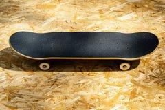 Faites de la planche à roulettes avec les roues blanches sur un fond en bois dans un skatepark Images stock