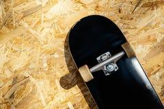 Faites de la planche à roulettes avec les roues blanches sur un fond en bois dans un skatepark Images libres de droits